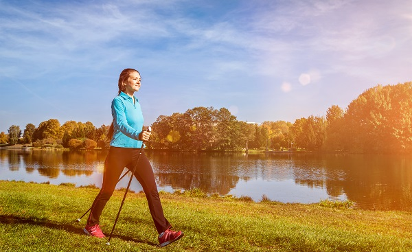 BASIS-SCHLIE Nordic walking adventure and exercising concept - woman hiking withnordic walking poles in park  With light leak and lens flare shutterstock 493512376